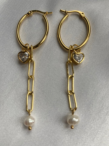 Gold earrings with pearl on a chain and a gold heart crystal
