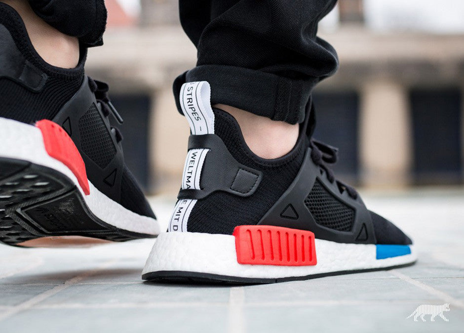 b9acf41dd1a8b ... the original NMD while the cage overlay gets a matching black. A  high-contrast white heel tab dons an international  The Brand With The  Three Stripes .