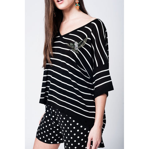 Black sweater with white stripes and bird detail on the front