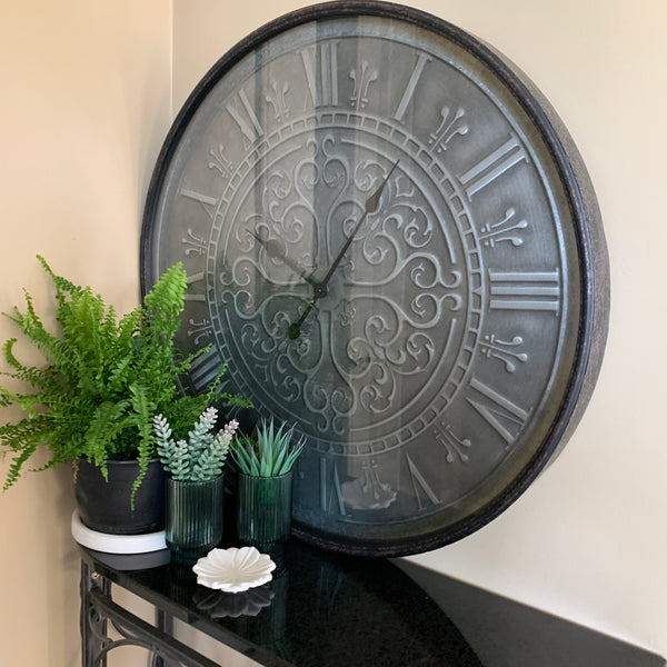 metal clock with roman numerals on brushed steel face