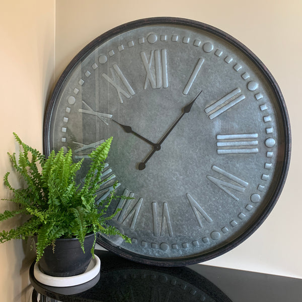 clock with roman numerals, framed in metal and glass