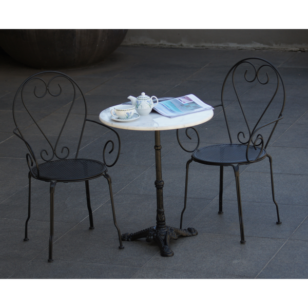 Outdoor patio setting Bella, marble top and cast iron base with 2 chairs with arms in black finish. Pictured on paving