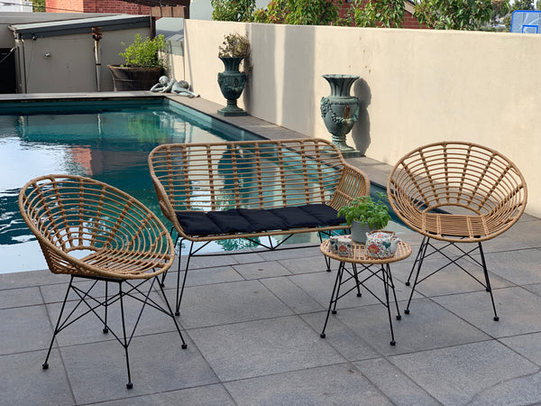 Outdoor patio setting Isla with bench seat, made from plastic/PU simulated cane, in natural cane finish. Pictured in a pool setting.