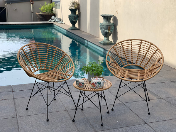 Outdoor patio setting Isla, 2 chairs and table, made from plastic/PU simulated cane, in natural cane finish. Pictured in a pool setting.