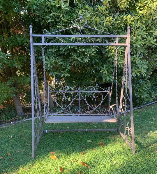 Outdoor Garden swing, made from metal in aged brown finish, pictured in a garden setting