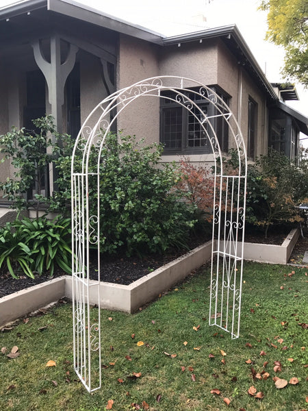 Wide metal garden arch in distressed cream in garden setting
