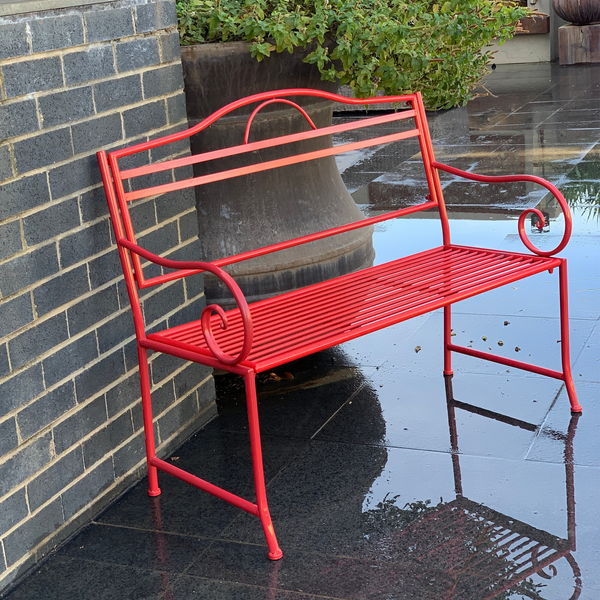 Outdoor garden bench Salsa, Made from metal in tones of red  colour, pictured on paving