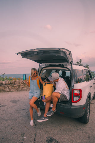 couple sitting on tailgate of car.