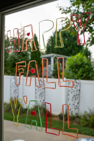 """Window decorated for Halloween and fall that says """"Happy Fall Y'all""""."""
