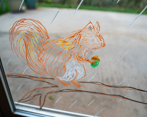 A squirrel drawn on a window with Kitpas window crayons for Halloween decoration.