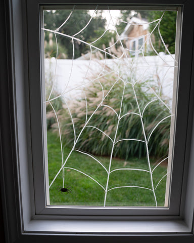 A spiderweb drawn on the window with Kitpas window crayons for Halloween decoration.