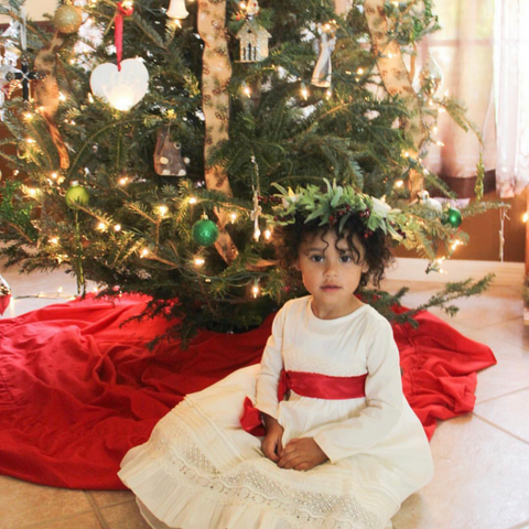 A small girl is dressed up as Lucia for St. Lucia Day. Bella Luna Toys