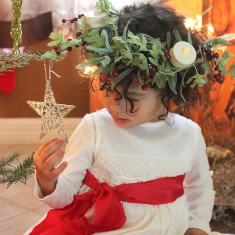 A young girl dressed as Lucia for St. Lucia Day - Bella Luna Toys
