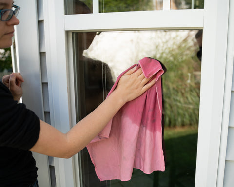 Someone washes a window with a red rag