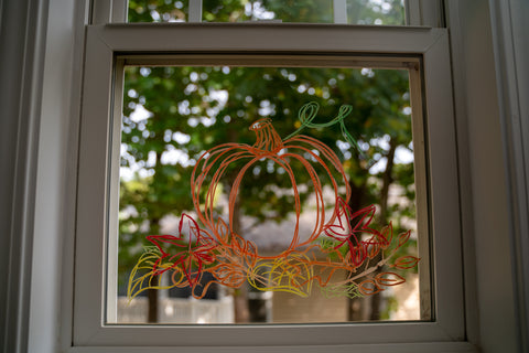 A pumpkin drawn on window for Halloween decoration with Kitpas window crayons