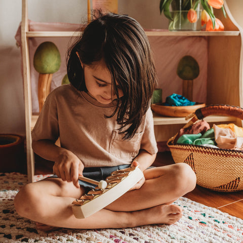 A child plays a pentatonic scale in a Waldorf playroom