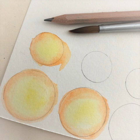 Yellow circles painted with watercolor with two brushes laying ontop of the paper.