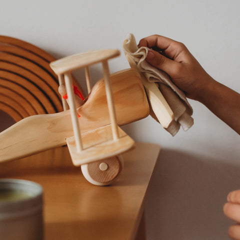 A hand wiping a wooden airplane with a cloth Cleaning and caring for wooden toys