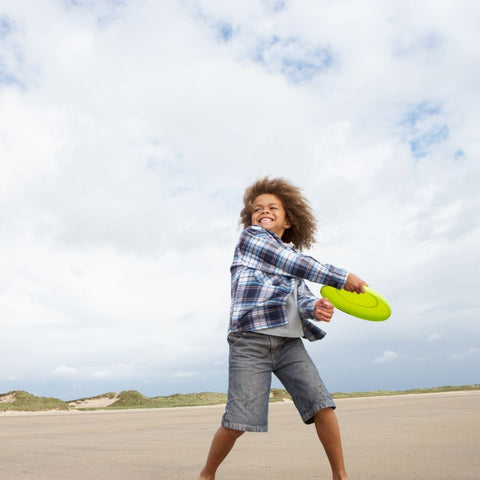 A child tossing a frisbee on the beach outdoor toys