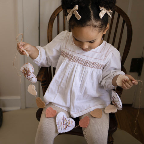 A young child holding a handmade Valentine Garland. Valentine's crafts for kids.