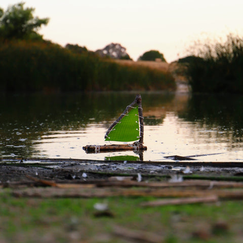 DIY toy raft made from sticks and leaves floating on the water