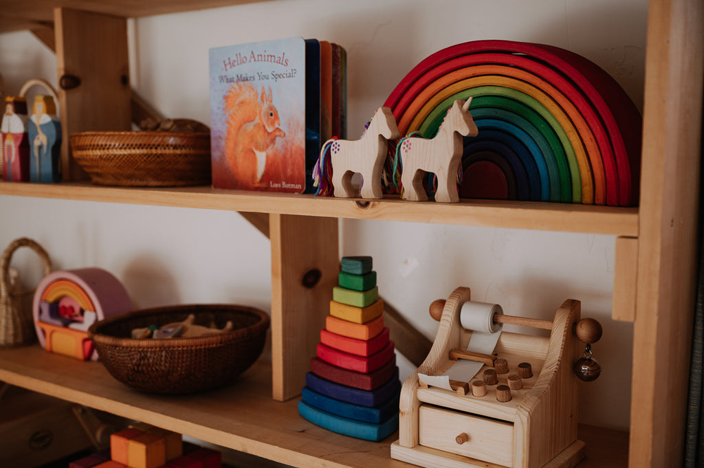 An assortment of wooden toys on a curated toy shelf