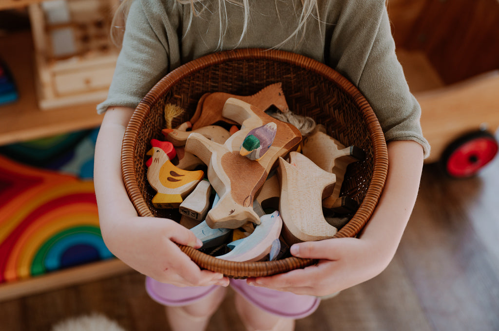 A child's arms hold a basket full of Ostheimer wooden animals from Bella Luna Toys
