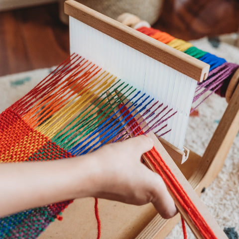 A child weaves with the Easy Weaver Loom from Bella Luna Toys