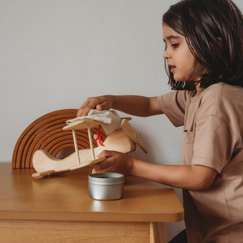 A child using Bee Luna Natural Beeswax Polish to care for wooden toy airplane