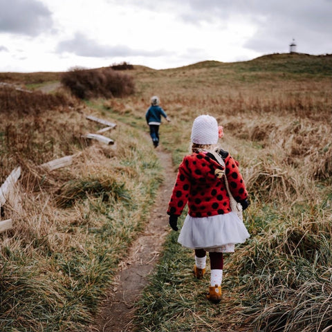 Hunt for signs of spring on a nature walk. Two children walking in the late winter.