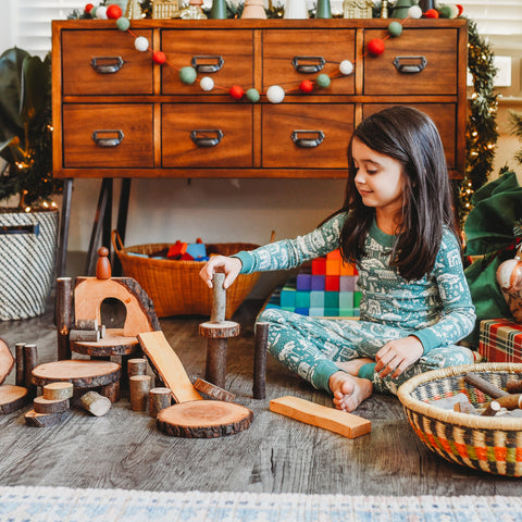 A child plays with a peg doll at stacked up Eco Blocks.