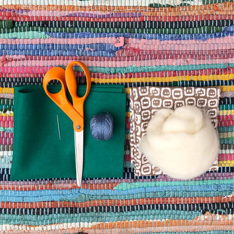 Scissors, fabric, needle, thread and wool laid on a table.