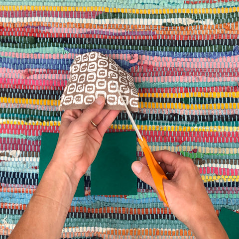 A hands only image showing how to cut the hat for the felt gnome holiday tutorial.