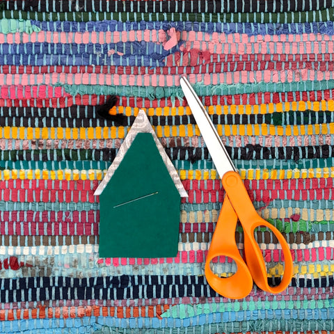 Pieces of frabric lay next to scissors for the felt gnome holiday tutorial.