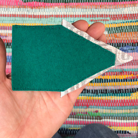 A hand holds the fabric in a horizontal orientation.