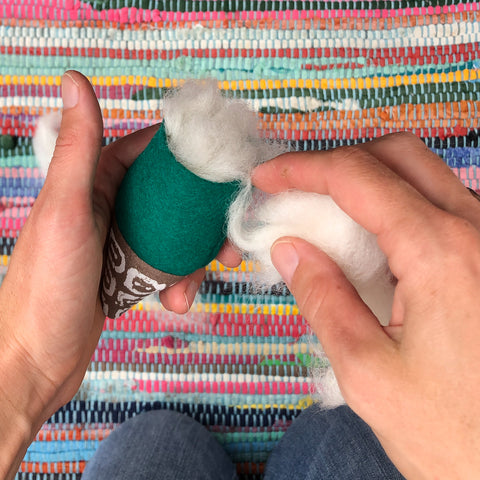 A hands only image, stuffing the felt gnome with wool.