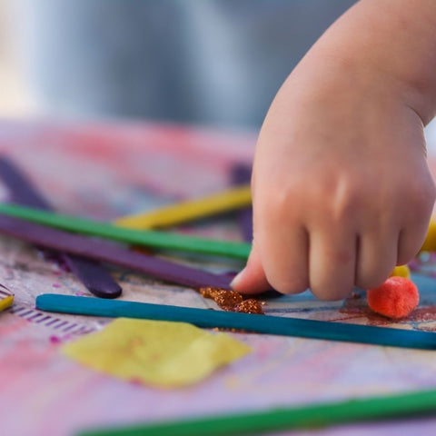 A child's hand gluing pieces to a collage.