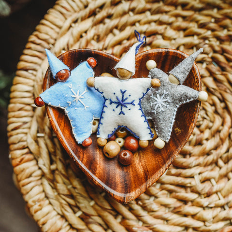 A wooden bowl containing wooden beads and 3 completed felt Waldorf Snowflake Children crafted dolls.