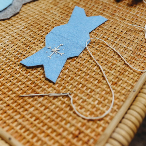 Tapestry needle and embroidery floss used to stitch a snowflake on the felt.