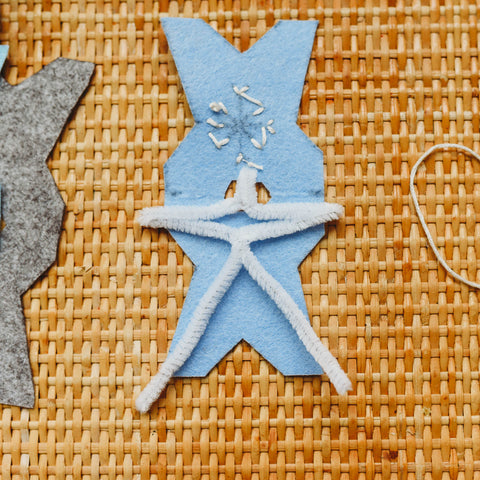 A pipe cleaner bent into a stick figure shape to give the waldorf snowflake child shape.