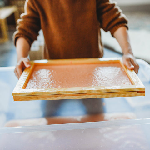 A child dipping screen into paper pulp to make recycled paper.