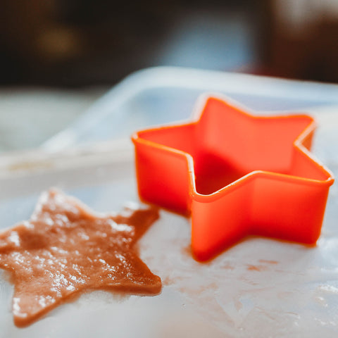 Cookie cutter being used to create star shaped paper.