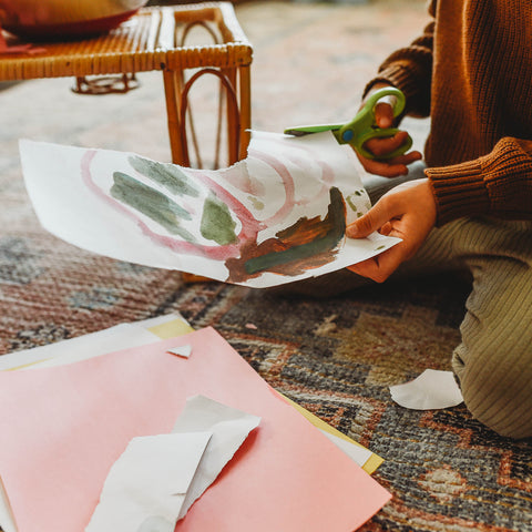 A child cuts up recycled paper to make diy thank you cards.