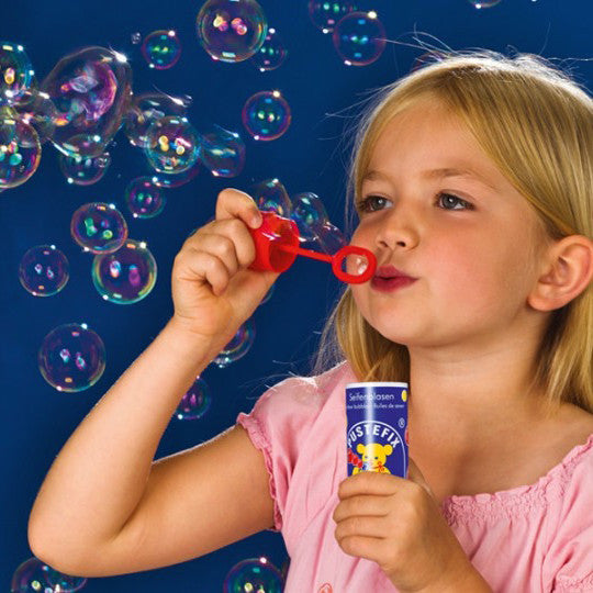 Girl blowing Pustefix bubbles