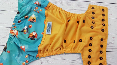 Fish Parade (marigold pul, seaspray awj, two toned snaps; orange caps, black pieces) <br>PK Wrap Around, One Size Pocket Diaper<br>Instock and Ready to Ship