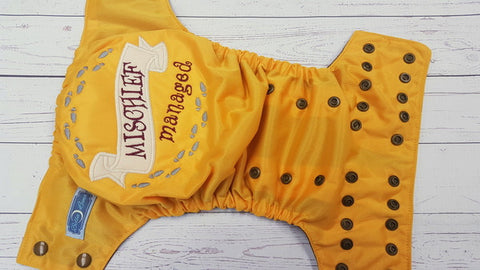 Marigold Mischief Managed Swear (brown awj, bronze snaps) <br>Embroidered, One Size Pocket Diaper<br>Instock and Ready to Ship