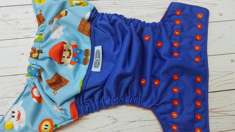 It's a Mario (royal blue pul, red awj, two toned snaps; marigold caps, red pieces) <br>PK Wrap Around, One Size Pocket Diaper<br>Instock and Ready to Ship