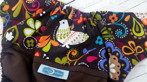 Norwegian Song Bird (chocolate outer, two-toned snaps - white caps / orange pieces )<br>Wrap Around, One Size Pocket Diaper<br>Instock and Ready to Ship