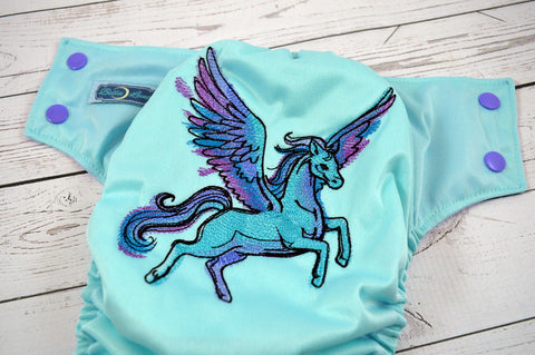 Pastel Pegasus ( seaspray outer, two-toned snaps - medium purple caps / light pink pieces)<br>Embroidered, One Size Pocket Diaper<br>Instock and Ready to Ship