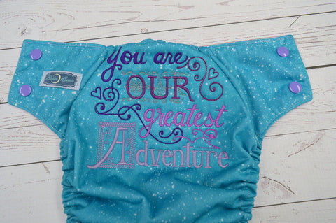 Our Greatest Adventure (speckled turquoise pul, lavender awj, med purple snaps) <br>Embroidered, One Size Pocket Diaper<br>Instock and Ready to Ship